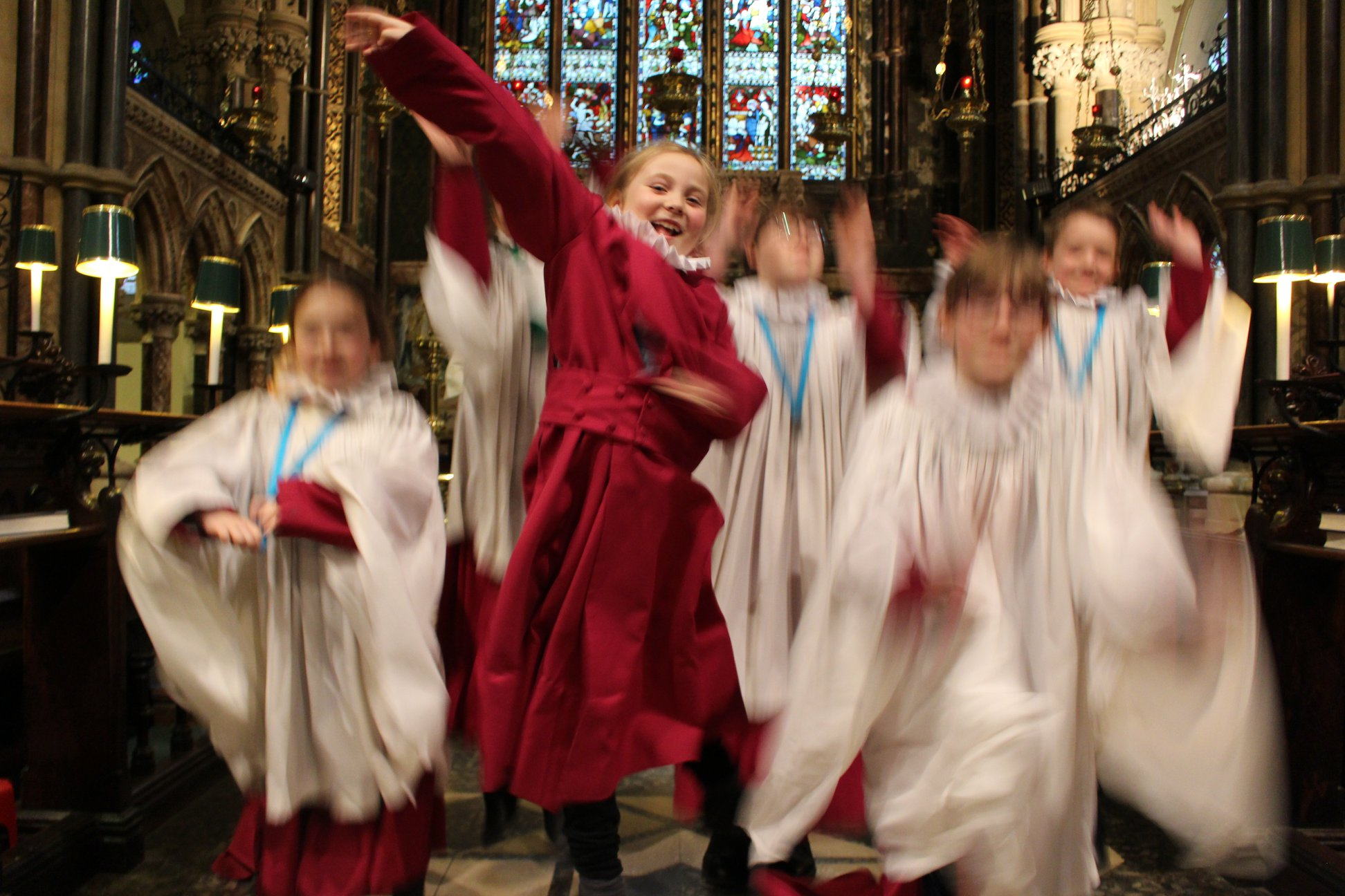 Trebles in the choir happy and jumping inside the church